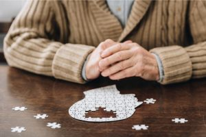 Äldre man som leker med pussel som ser ut som en hjärna