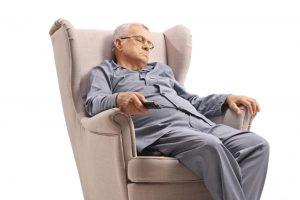 Äldre man som sitter och somnar i en soffa