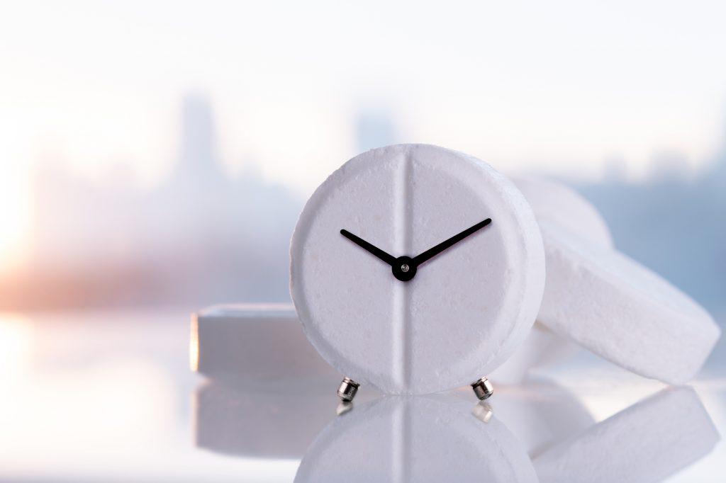 Väckarklockatablett på en vit speglad yta med kopieringsutrymme. Läkemedel med en klocka på en bakgrund av morgonstaden med en gryning.